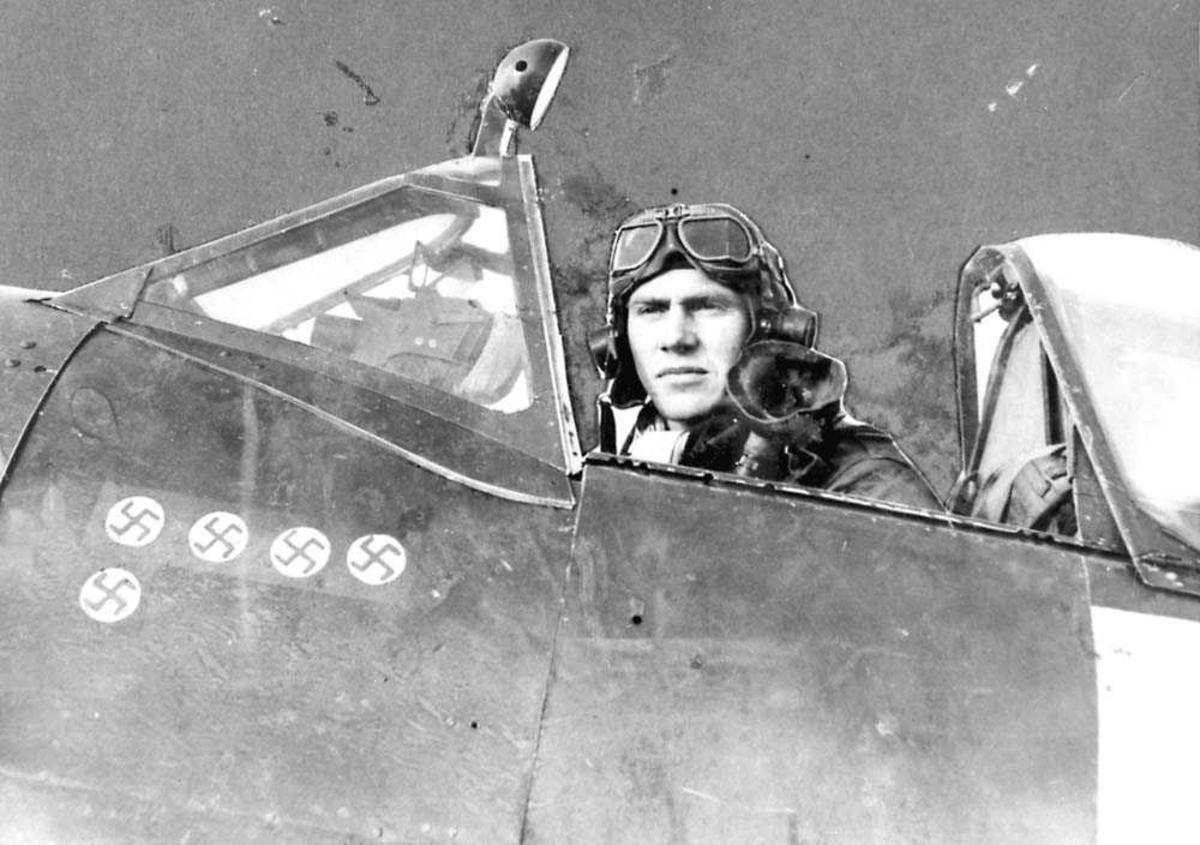 Portrett. En person som sitter i en flycockpit. Har flyuniform på seg.