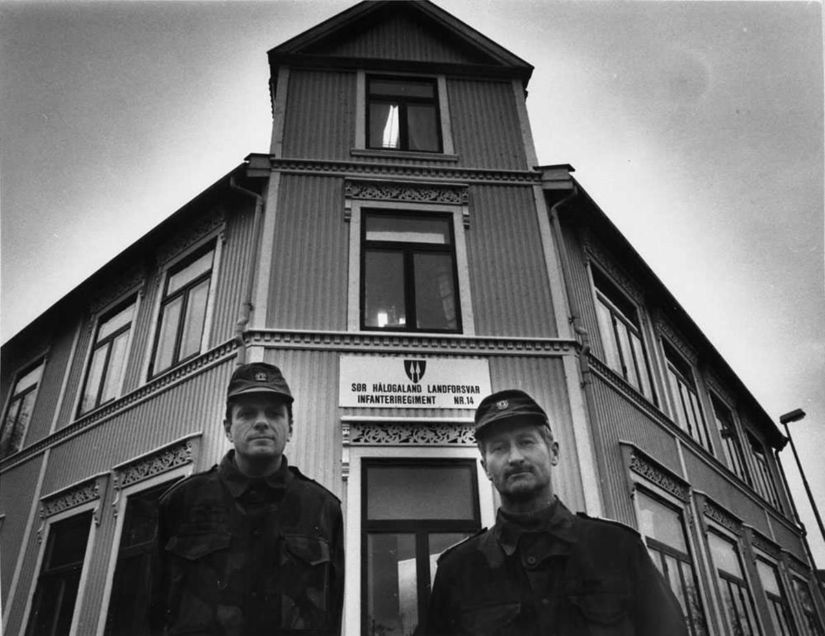 """To personer som står foran en bygning, menn i militæruniform. På bygningen står det et skilt med """"Sør Hålogaland landforsvar infanteriregiment nr. 14""""."""