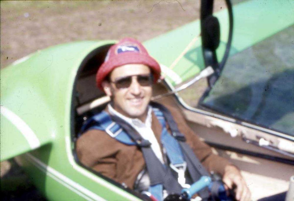 En person, mann, som sitter i cockpiten på et seilfly.