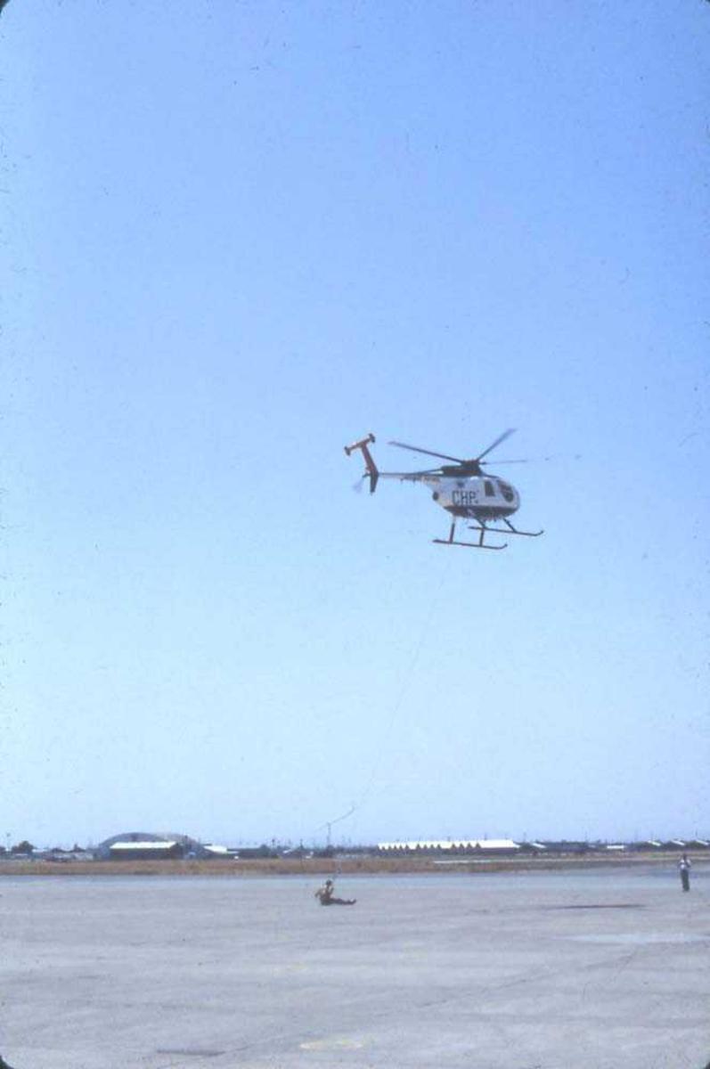 Flystevne. Ett helikopter i luften, Hughes 500. En person sitter på bakken og er festet til en line som går til helikoptret. En annen person til høyre. Bygninger i bakgrunnen.