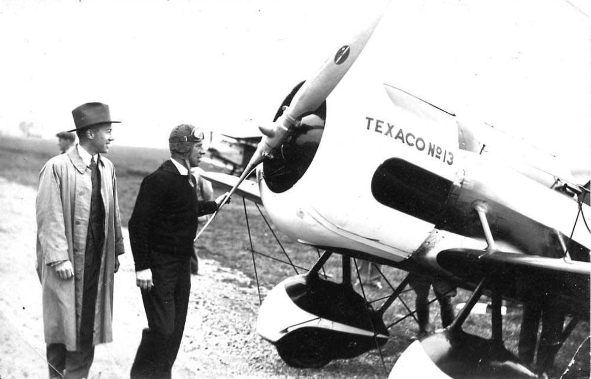 "Ett fly på bakken, Travel Air modell R ""Mystery S"" NR1313. To personer foran flyet."