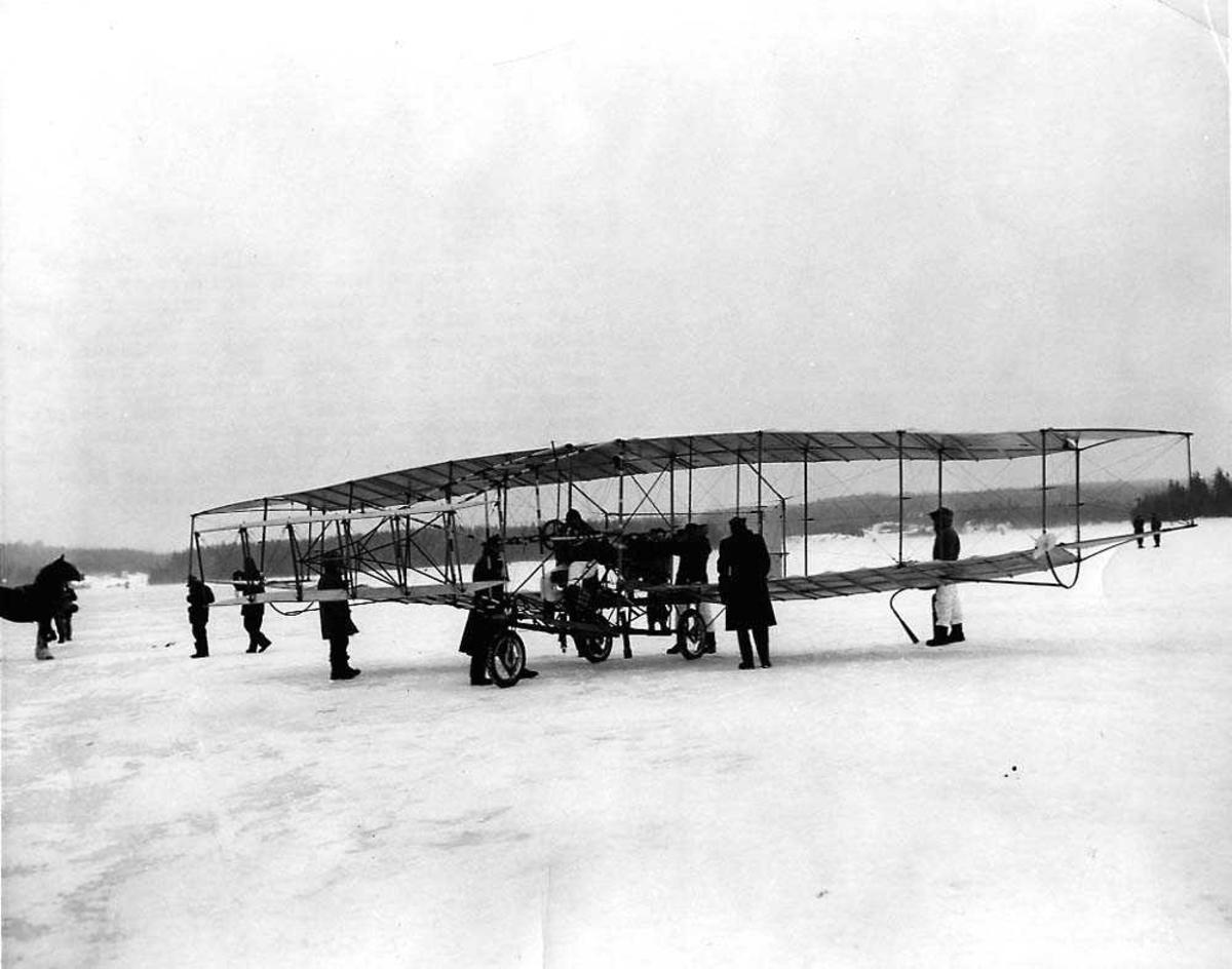 Ett fly på isen, Silver Dart II Biplane. Flere personer ved flyet.