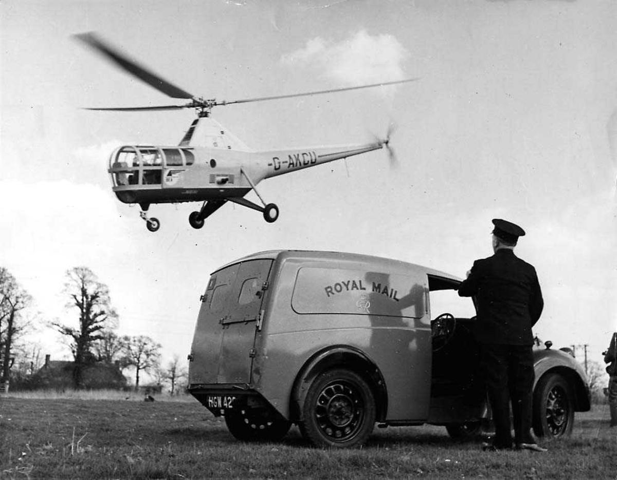 Ett helikopter i luften, Westland Sikorsky S.51 Mk. 1A Dragonfly G-AKCU. En postbil med en person  ved sidan av, på bakken.