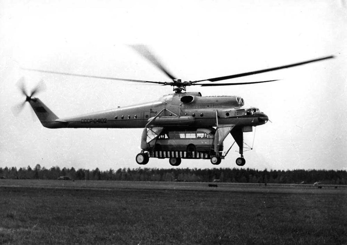 """Ett helikopter i luften like over bakken, Mil Mi-10 (V-10) """"Harke"""" flying crane. En buss henger under helikoptret."""