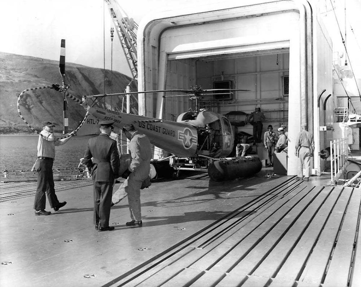 """Ett helikopter som blir lastet ombord i """"hangar"""" på en båt. Bell 47 J Ranger HTL-7. Flere personer rundt helikoptret."""