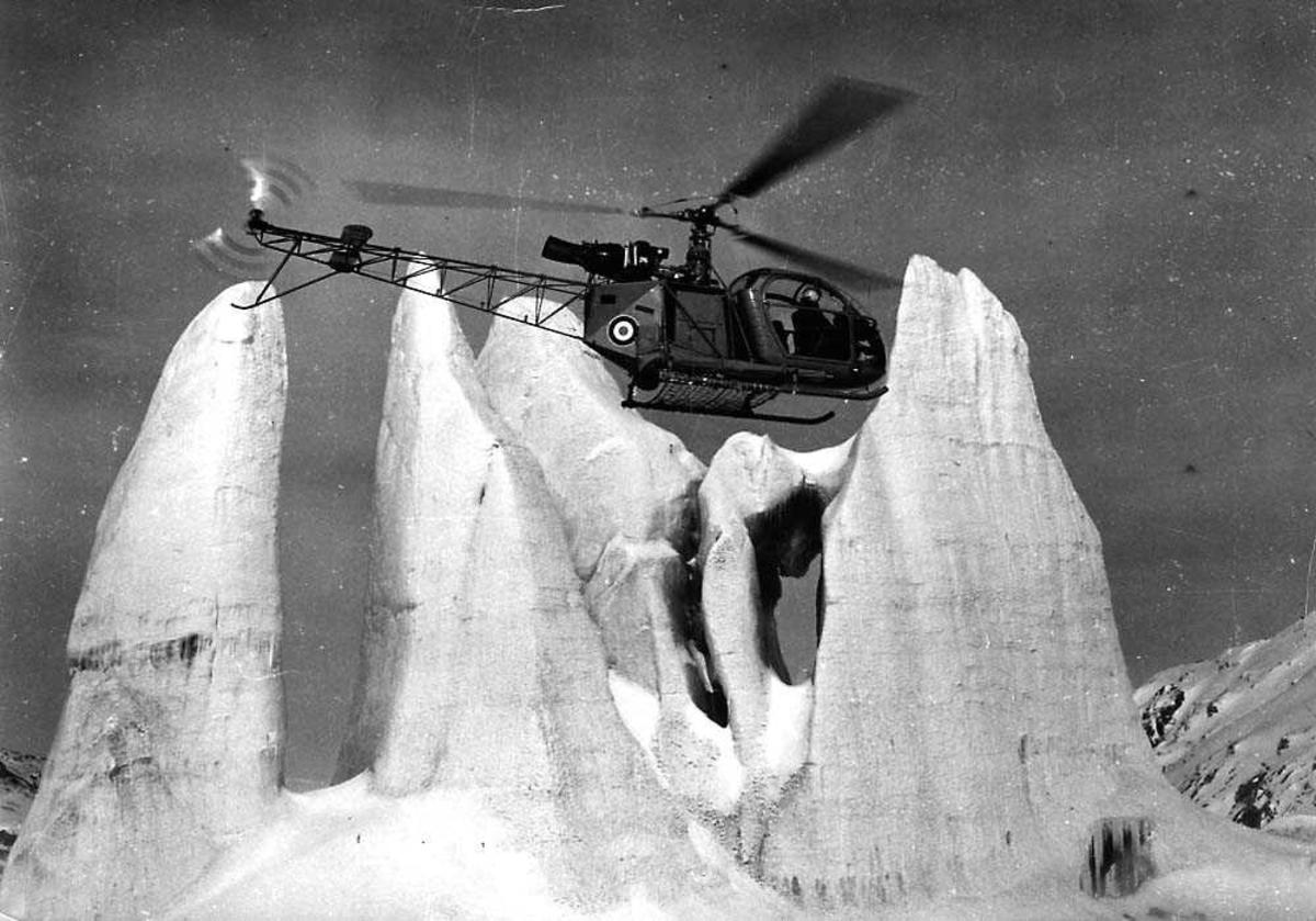 Luftfoto. Ett helikopter i luften, Aerospatiale Alouette. Fjell i bakrunnen.