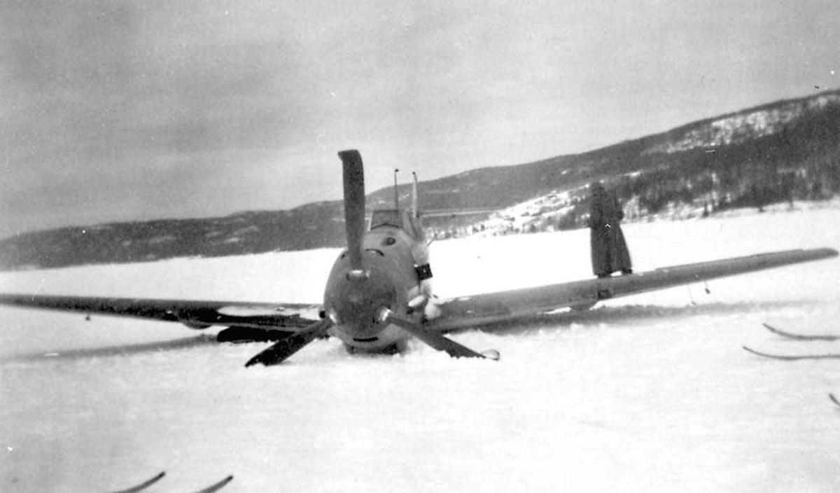 Ett havaret fly som ligger ute på et snødekt vann, Messerschmitt Me 109. En person står bak flyet. Fjell i bakgrunnen.