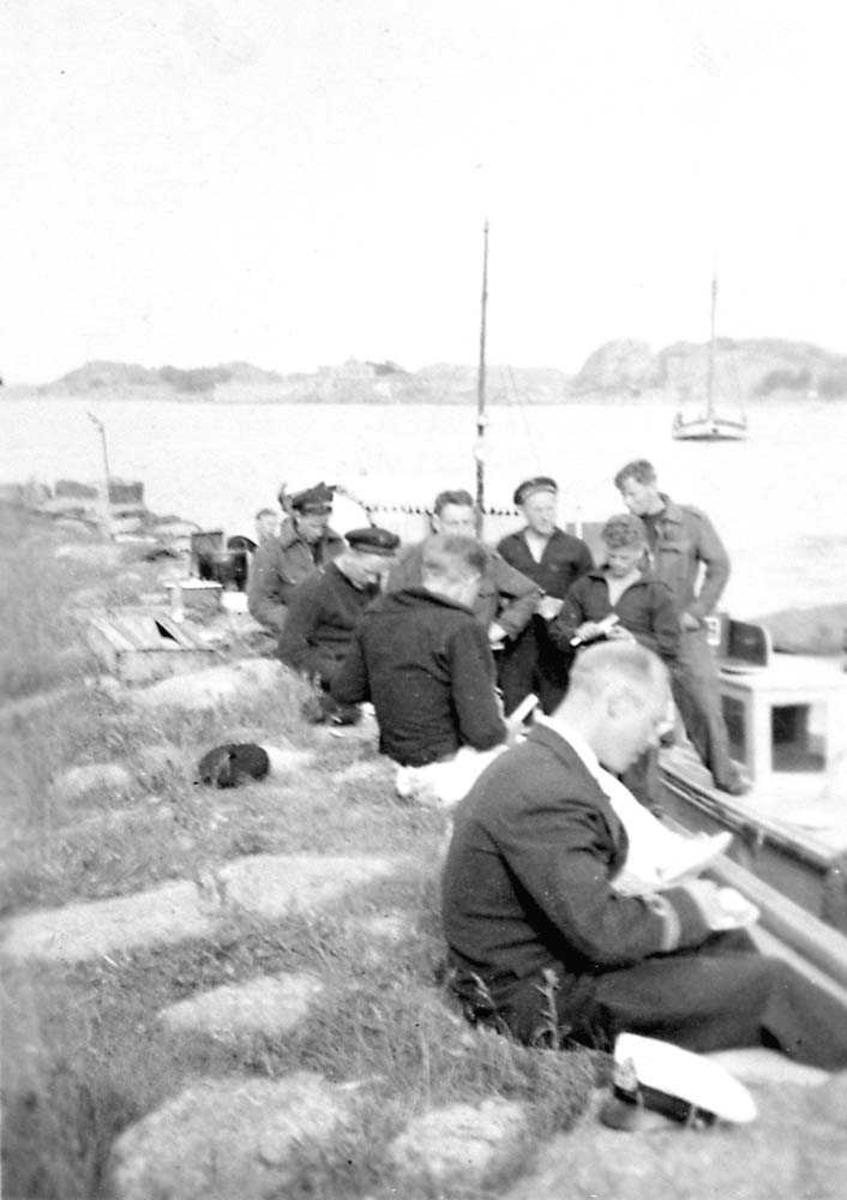 Flere personer som sitter ved en båt som ligger ved kai.