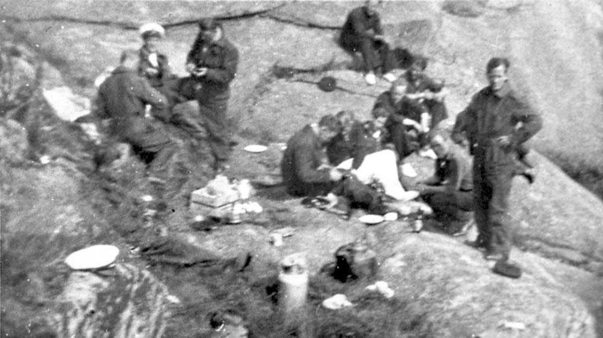 Gruppefoto av flere personer som sitter/står på et svaberg.