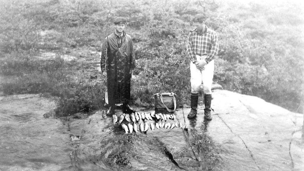 To personer, med fangsten med fisk som de har fanget, mellom seg.