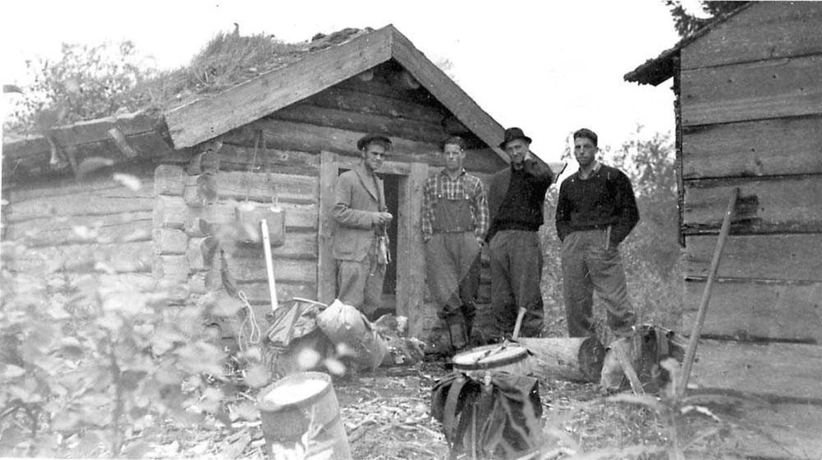 Fire personer som står mellom to tømmerhytter.