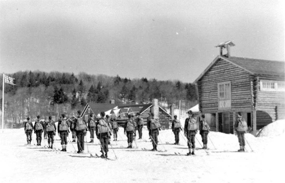 En tropp med rekrutter som står på en plass foran noen tømmerhytter. Rekruttene har ski bå beina og ryggsekk på seg..Snø på bakken.