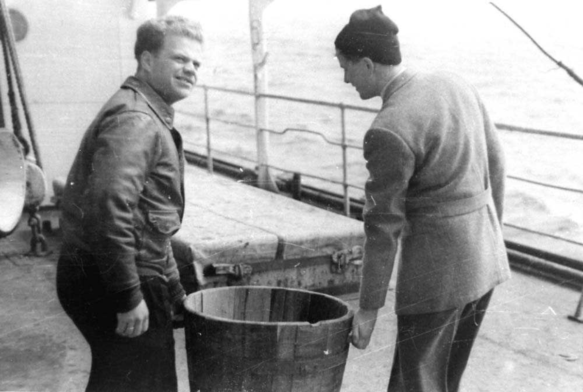 To personer som bærer en stampe mellom seg, ombord på en båt.
