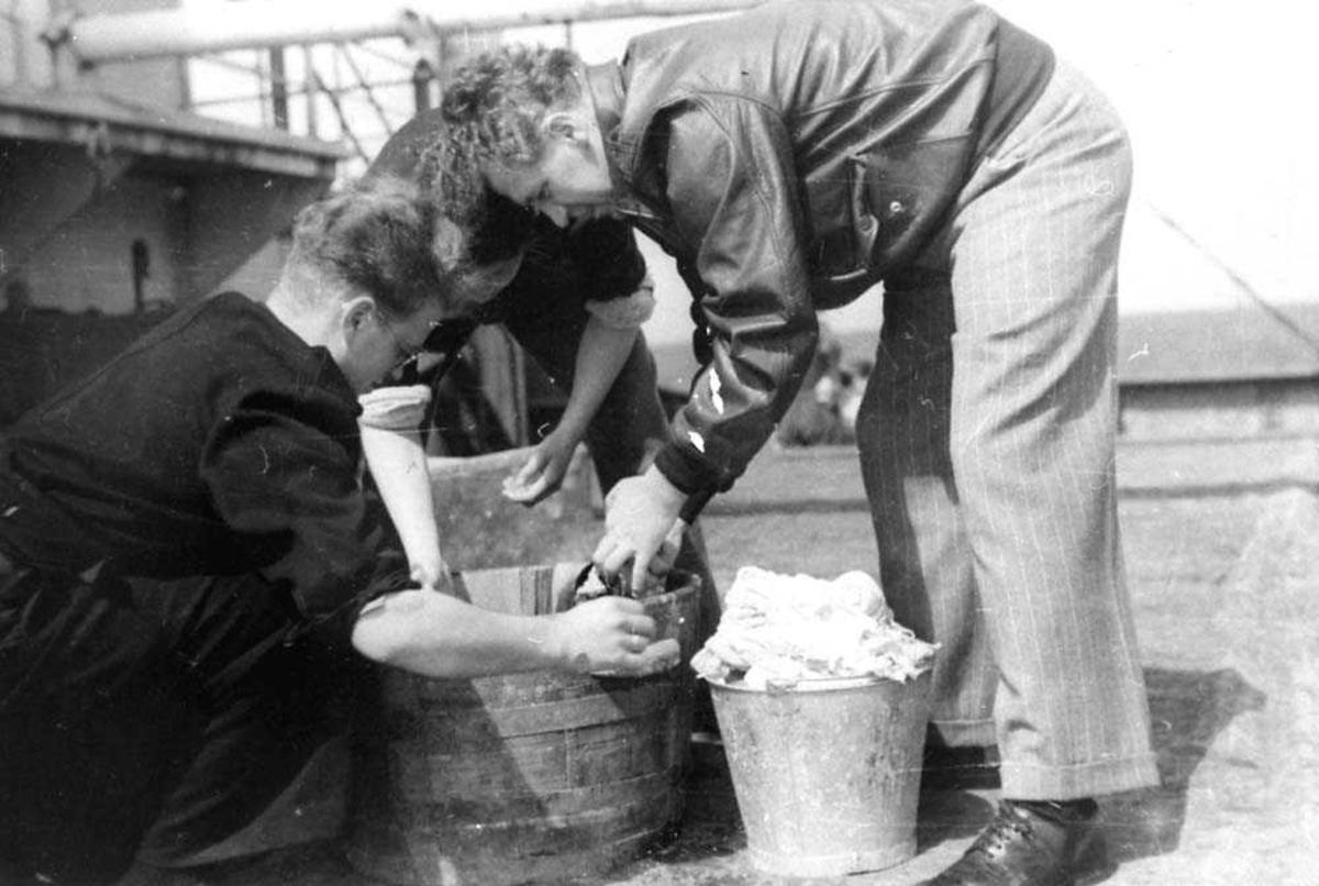 Tre personer som vasker noe tøy i en stampe.