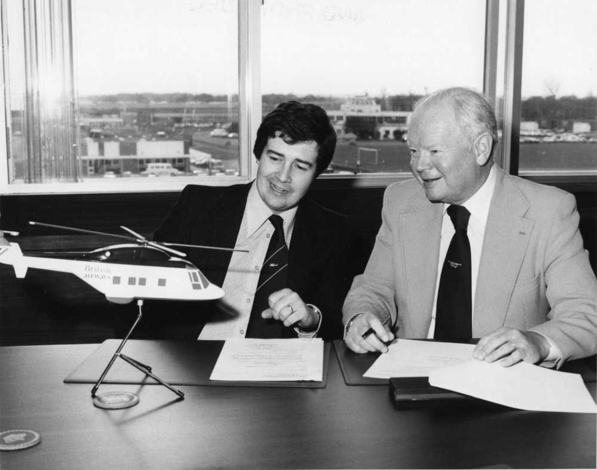 2 menn ved bord. Helikoptermodell til venstre. Kotraktsignering.