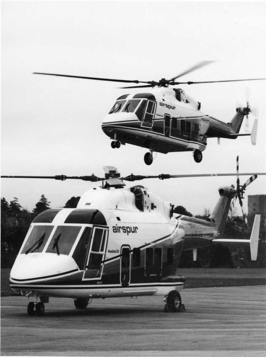 2 Helikopter; ett i luften, ett på bakken. Westland 30 (N5830T og N5820T) med Airspur farger.