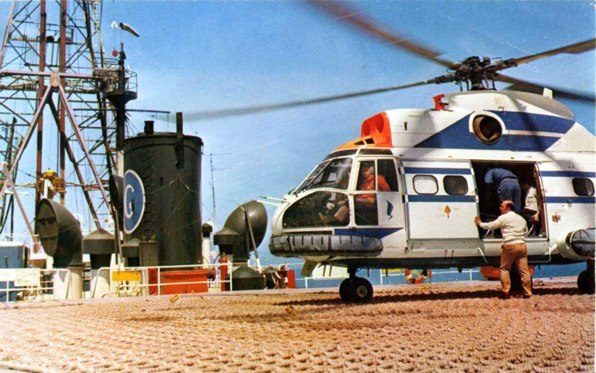 Ett helikopter på bakken/helipad på plattform/rigg. Aerospatiale/Westland  SA330F/G Puma. Mennesker på vei inn i helikopteret. Boretårn ses t.v.