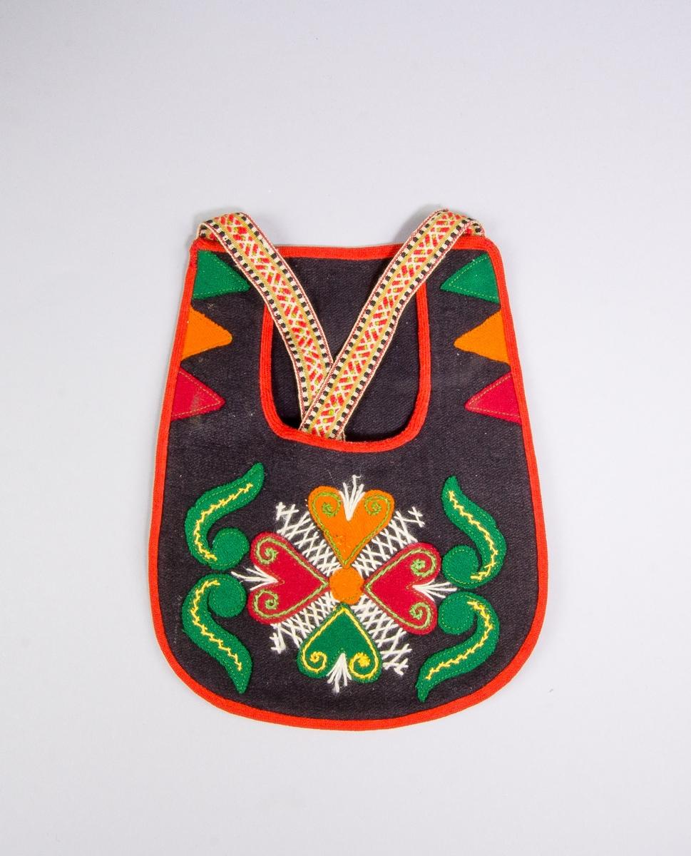 Kjolsäck inspirerad av kjolsäckarna från Leksands socken, Dalarna. Modell med u-formad öppning. Tillverkad med framstycke och bakstycke av svart ylletyg, med applikationer av kläde i grönt, mörkrött och orange, fastsydda med maskin. Motiv: centralt placerad hjärtblomma med slingor och trekanter på sidorna. Broderi utfört med bomulls- och konstsilkegarn i vitt, grönt och gult: flätsöm, stjälksöm och sticksöm. Kantat runtom med rött diagonalvävt ylleband. Midjeband handvävt, med plockat mönster i rött ullgarn på vit botten, kantränder i grönt och svart, hakar och trådtränsar.