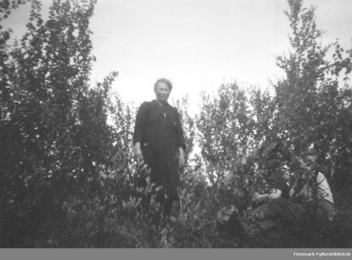 Elen Aslaksen som står inni et kratt på plassen Ruselv i Kokelv. Hun er kledt i en mørk kjole. Det sitter flere personer på bakken