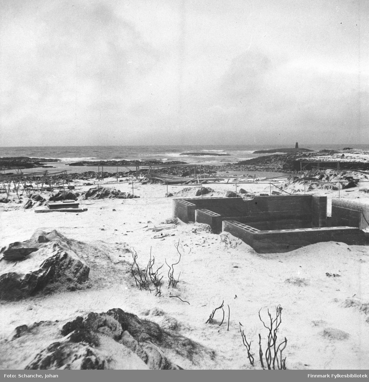 Oversiktsbilde over Berlevåg i gjenreisningstid.  En grunnmur er reist opp for et nytt hus (muren ser nybyggdt ut).  Tomme fiskehjell ved fjære. Lengst bak et lite fyr.