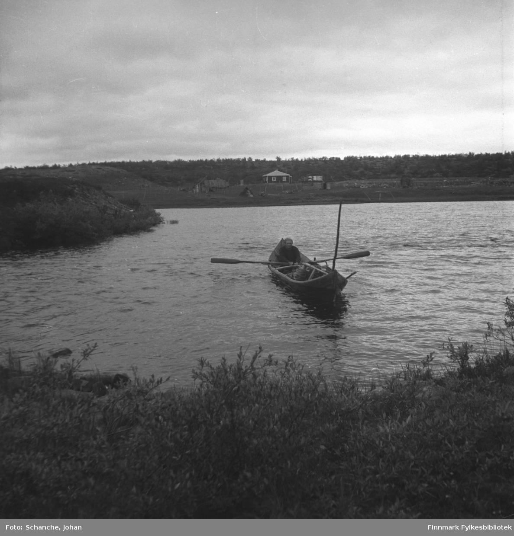 En mann ror en båt mot Lappoluobal fjellstue sommeren 1947. Fjellstuen ligger på andre siden av vannet.