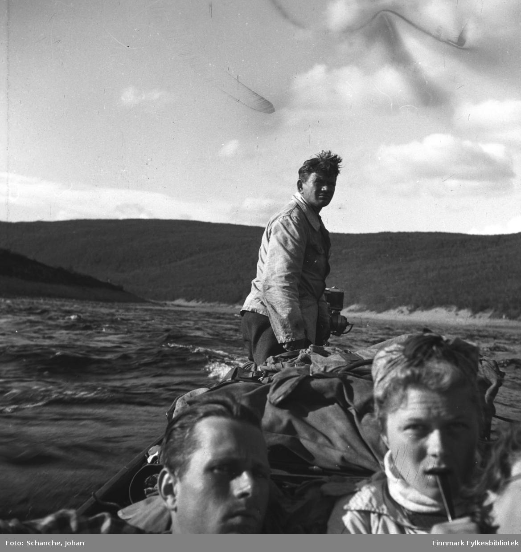 Bildet er tatt ombord på elvebåten: vi ser ansiktet til en mann og en kvinne som sitter midt på båten. Bak på båten står en mann og styrer. Bakerst fjellene.