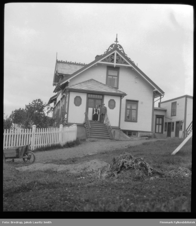 En mann og en kvinne står på trappa til Esbensens hus i Nyborgveien.  Foran huset et fin hage med busker og trær, en trillebår står parkert i nærheten.
