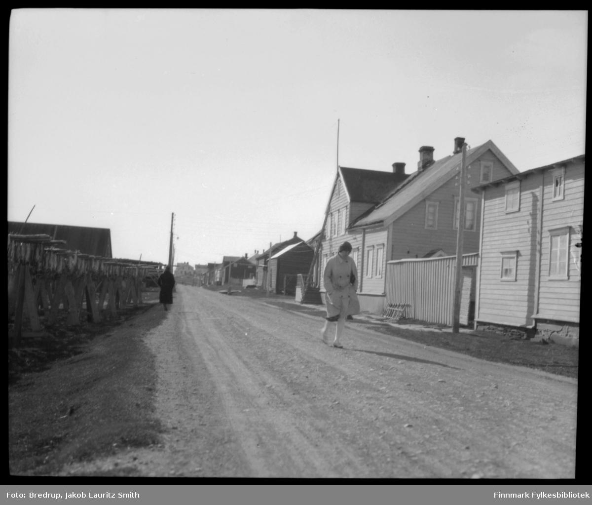 En kvinne strever seg mot vinden på vei utover langs Hvistendahlsgate fra Vadsø sentrum.  I bakgrunnen flere bolighus.  Hun passerer akkurat Esbensengården på Sletten.  På nedsiden av veien hjeller med masse tørrfisk.