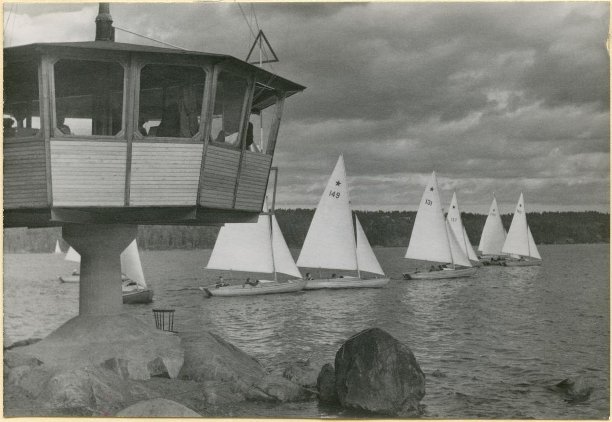 Övrigt: Denna bild är tillsammans med KSSS-samlingens Fo133681 - Fo133683 samt Fo133684 - 687 monterad på  kartongblad ur album. Flera av dessa bilder är från Skolungdomens höstseglingar på Baggensfjärden i Saltsjöbaden i september 1951, och åtminstone två av dem är tagna av Oscar Norberg; det är möjligt men inte belagt att även Fo133680 tagits av Norberg under dessa seglingar  (jfr Fo133683 och Till Rors årg. XVII [1951] nr 20 s 19).  På Fo133680 ses fr v t h först tre skymda oidentifierade stjärnbåtar, därefter stjärnbåt 149 KORKIS, 131 NALLE PUH, 127 I-OR (skymd), 244 CHRISTINA (skymd) samt, längst t h, 140 BOLOMA. Samtliga dessa båtar deltog i ungdomsseglingarna i september 1951 (se seglingsprotokollet från finalseglingarna i KSSS årsbok 1952 s 178).