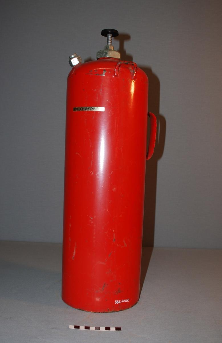 Vannapparat. Sylindrisk beholder avrundet mot toppen, der det er en ventil med ventilratt . Øverst på siden av beholderen en metall stuss for slange. Håndtak øverst på siden av beholderen der det også er en festebrakett.