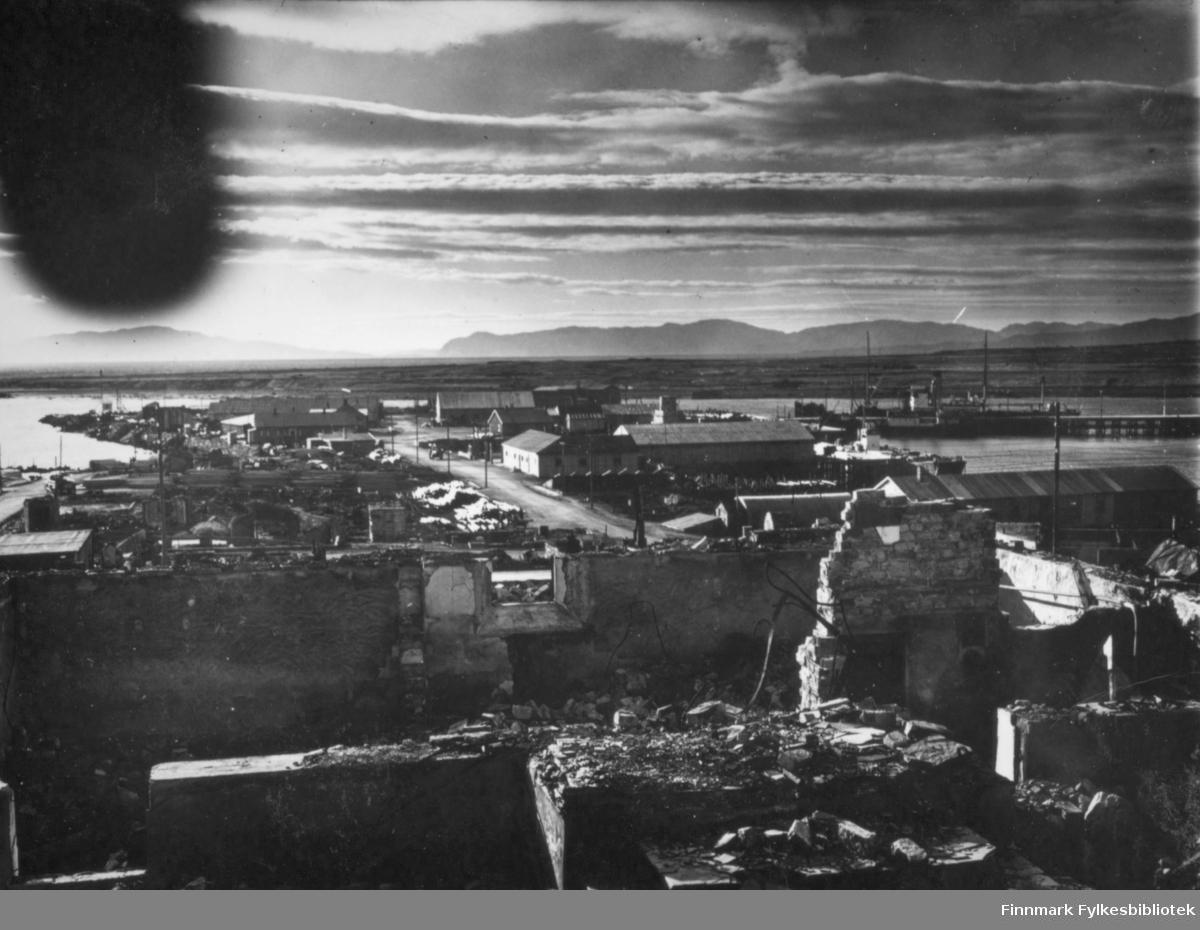 Sentrum av Vadsø fotografert ned mot havna, august 1946. I forgrunnen av bildet er det ruiner etter ødelagte hus, men lenger nede mot dampskipskaia har det allerede kommet opp lagerbrakker. Tollbodgata går midt i bildet