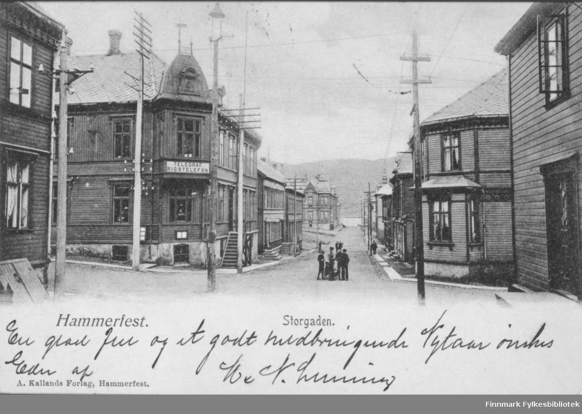 Postkort med trykt tekst: 'Hammerfest. Storgaden. A. Kallands Forlag, Hammerfest' Bygning nr 2 på venstre side av gata har skilt 'Telegraf. Rigstelefon'. Sendt som julekort
