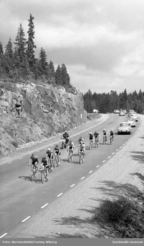Sverigeloppet på cykel. Cyklisterna kommer norrifrån, passerar Wästerlunds konditori vid Sandöbron och kommer fram till Hedbergska skolan i Sundsvall.
