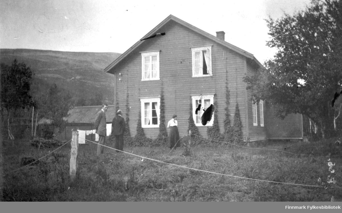 To menn og en dame står utenfor et hus i Rassejåkka i Tana en fin augustdag i 1916. Humle pynter veggen. Det var nok en nytteplante. I bakgrunnen henger det klær til tørk på en snor. På venstre siden av huset ligger det et uthus.