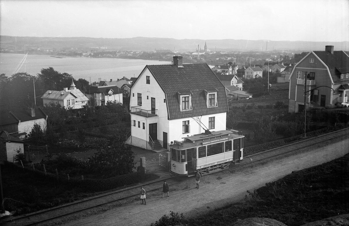 """Spårvagn som går mellan """"Bymarken - Stadsparken - Kasernerna"""". På vagnen står även texten """"9 Jönköpings spårvägar 9"""". Här har den gjort ett stopp på Bymarken. Tre flickor står på vägen som går längs med spåret."""