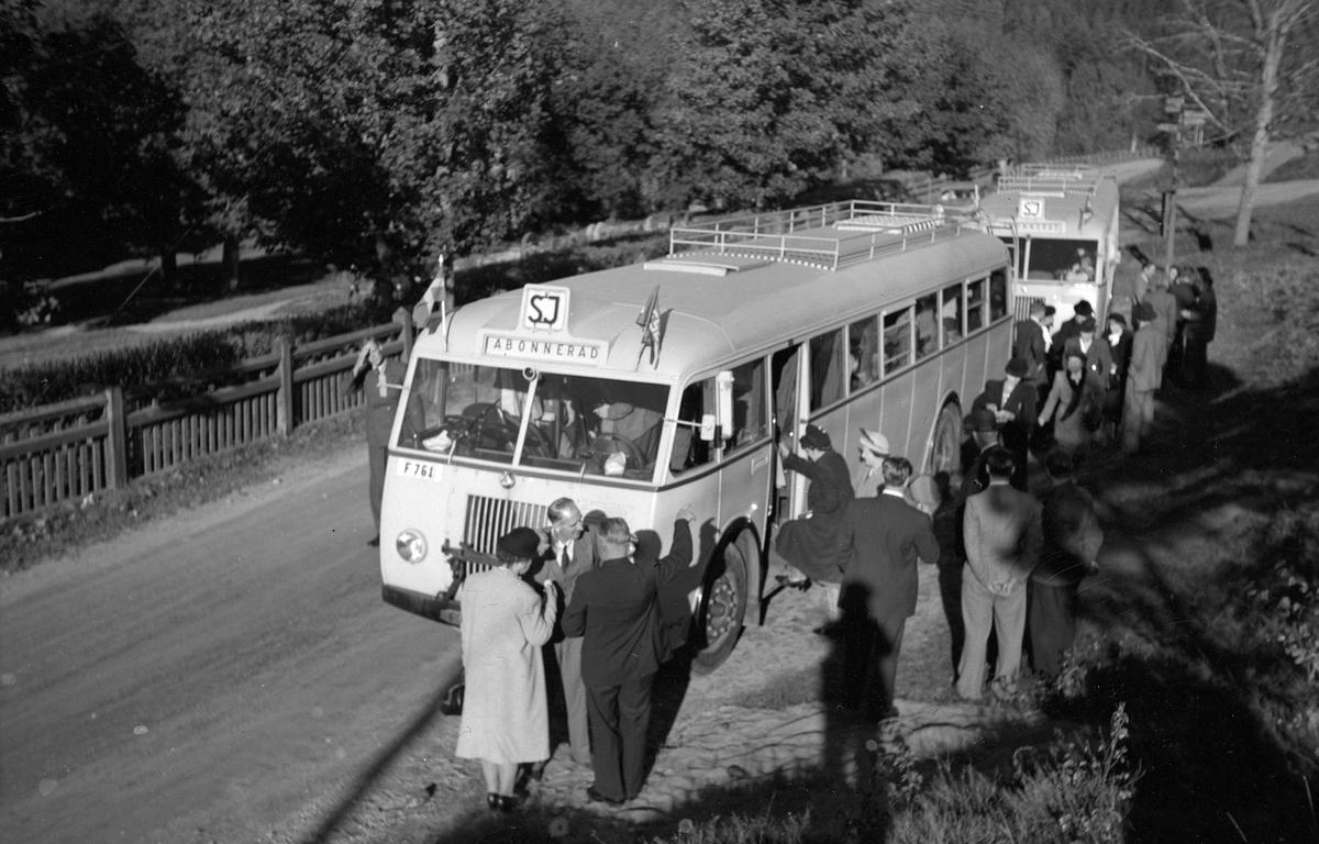 Två abonnerade bussar med passagerare utanför.