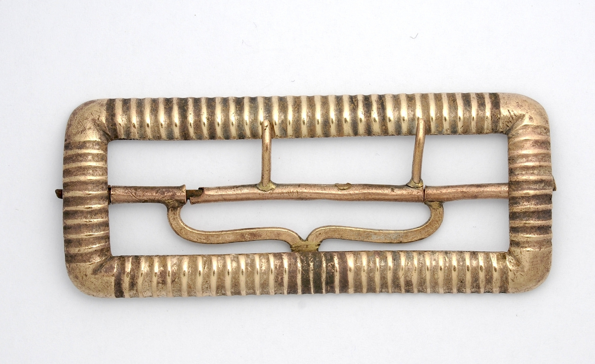 Beltespenne i messing. Tre spennenåler er lodda til koparsylindar, som kan dreiast om tverrbjelken. Denne er lodda til ramma. Beltespenna er forma som eit avlangt serpentinerkryss. Spenna er kobla til koparsylindrane, som er smidd rundt tverrbjelken. Ein av spennenålene manglar.
