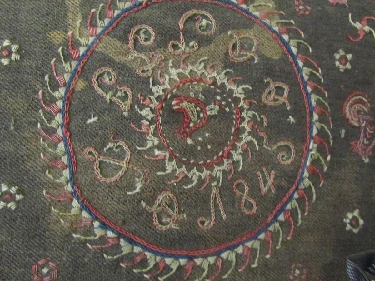 Blomar, fuglar, sirklar (solhjul), sirkulært midtfelt med årstalet 1845 og initala I G J D (truleg), akantusranke langs kanten.