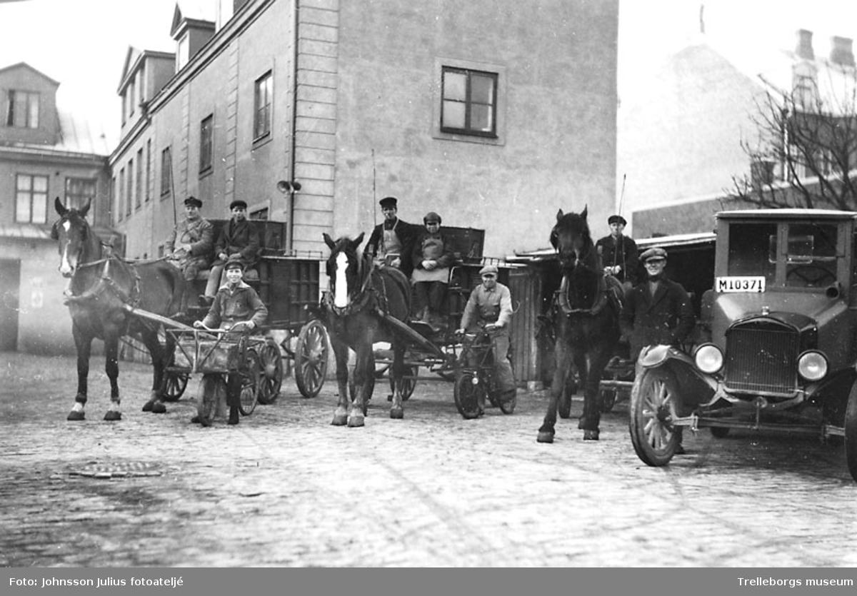 På Aktivs gård år 1930 står flera utkörare med sina tre hästvagnar, lastbil och två cyklar.