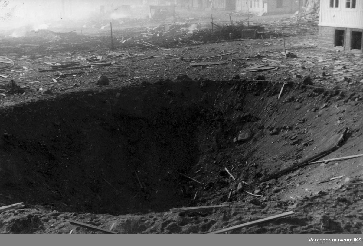 Bombekrater i skolegården i Vadsø. Skolebygningen øverst til høyre i bildet.
