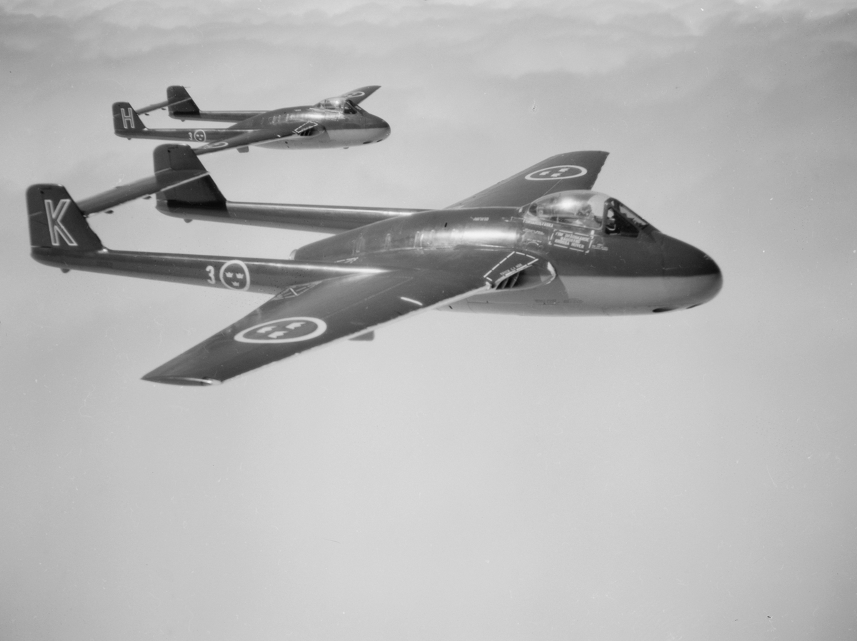 Två stycken flygplan J 28 från F 3 Malmen flyger i rote. Vy från sidan.