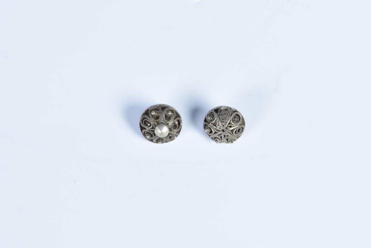 Tre knapper av sølv med filigransarbeid.