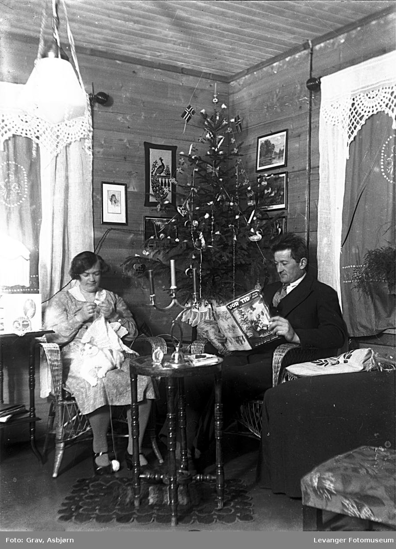 Gruppebilde. Ektepar med avis og strikketøy i en stue.