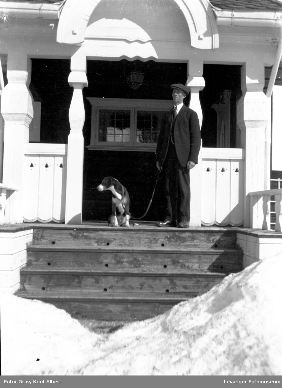 Mann med hund på trapp i et inngangsportal.