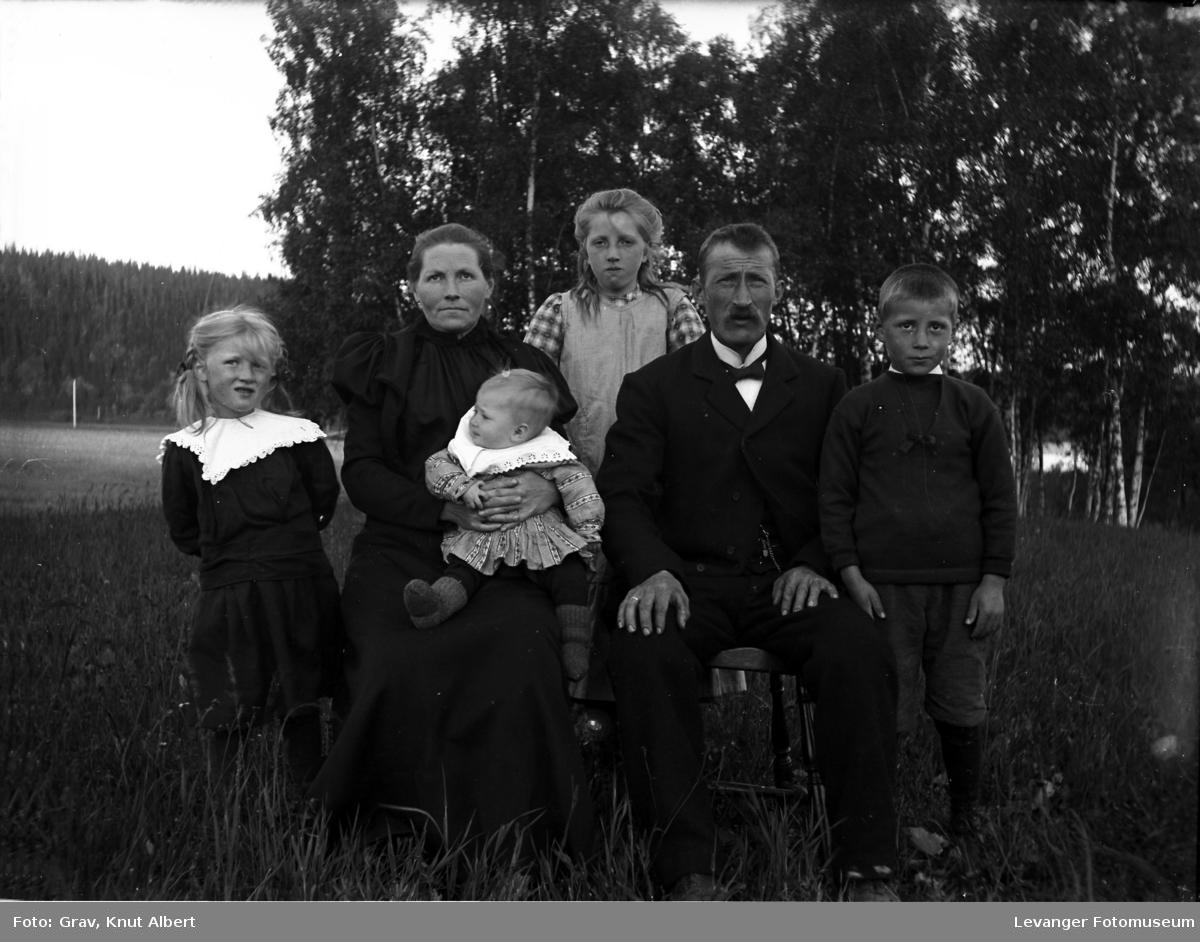Gruppebilde. Familie med fire barn fotografert utendørs.