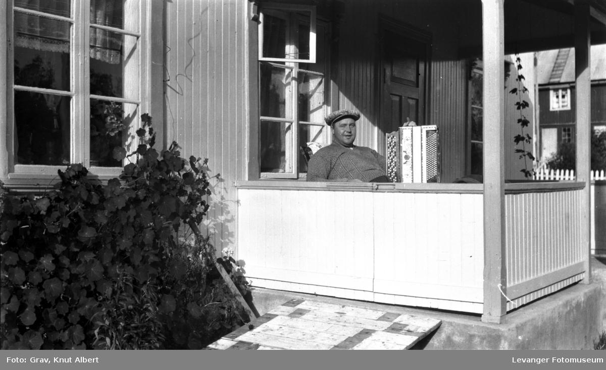 Portrett. mann med trekkspill på veranda