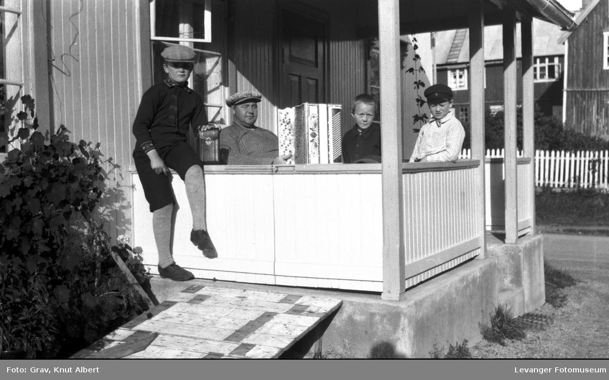 Gruppebilde, mann med trekkspill og gutter på veranda