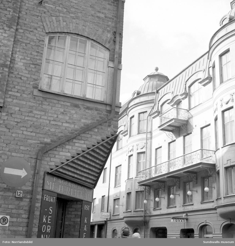 Gatubilder från Sundsvalls stenstad. Korsningen Nybrogatan-Kyrkogatan med Hotell Continental, Hotell Svea, Knaust Gillestuga och diverse butiker.