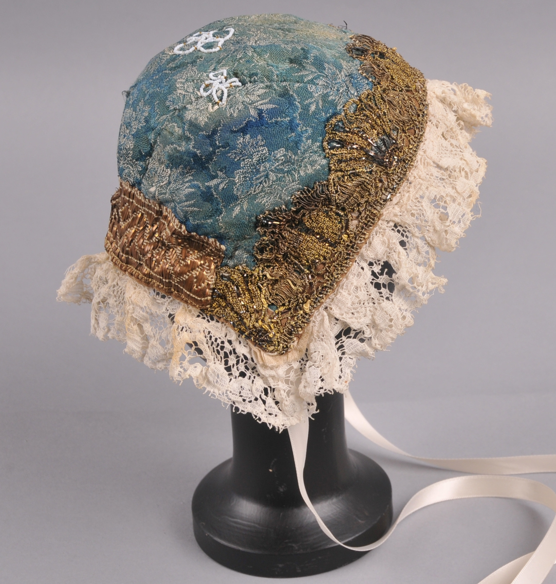 """Luve i blåmønstrete silkedamask, med gullknipling framme og gullband (admiralband) nede. Luva er samansett av tre delar (trebladluve), eit midtstykke og to sidestykke. Langs ytterkanten, rundt heile luva er det ein 5 cm brei bomullsblonde. I hjørna nede, på yttersida er det """"spor"""" etter knyteband som er avklypte. På same stad, men på vronga er det sauma på nye knyteband av polyester. Luva har blomedekor av små kvite perler, tre stk, på nakkestykket, med form som som ein hvalknute."""