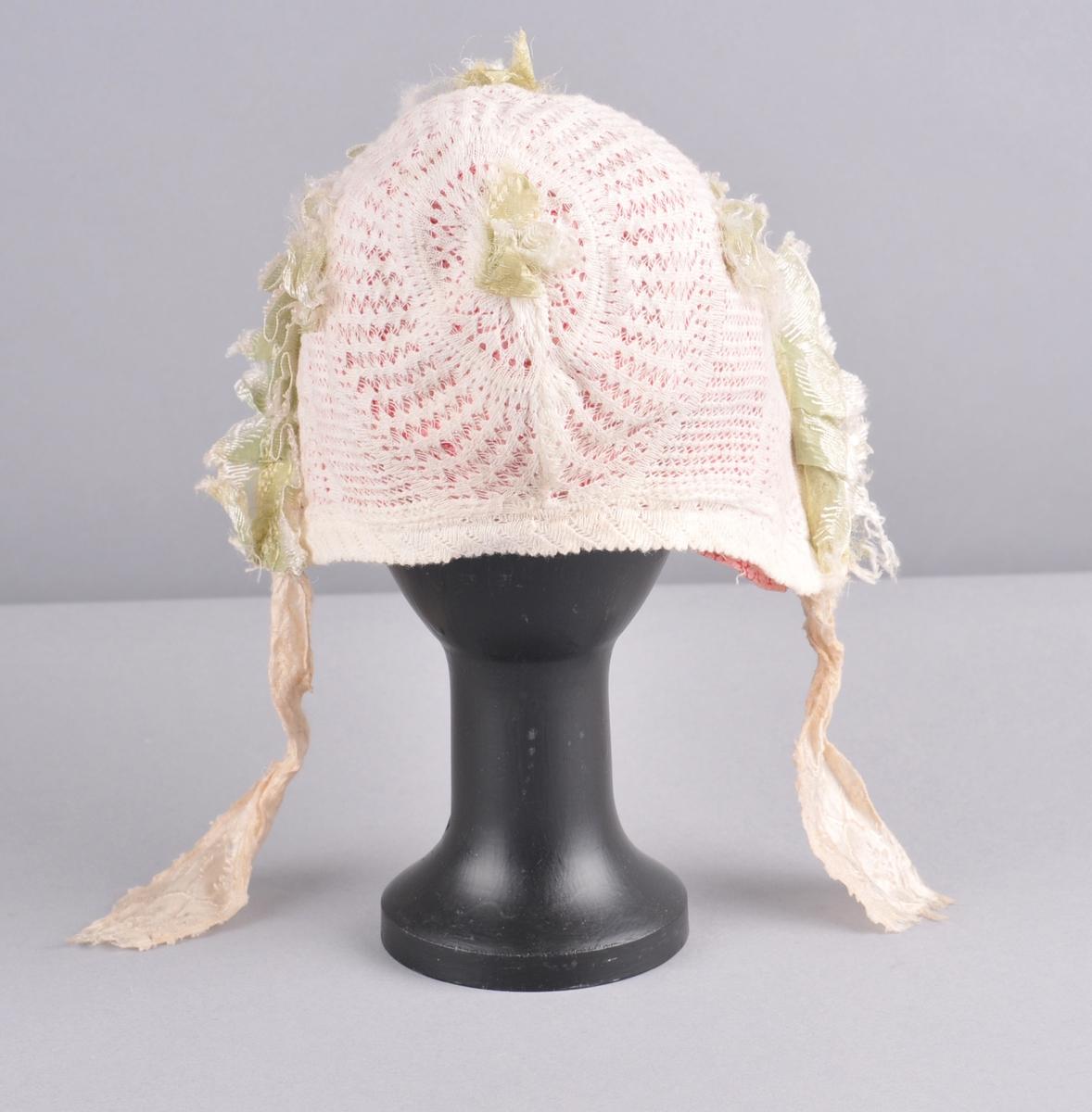 Maskinstrikka, fabrikkert, kvit luve av bomull. Luva har kyseform og fastsauma innerluve med  blondekant. Luva er mønsterstrikka og dekorert med grønt og kvitt silkeband, ei sløyfe oppå hovudet, ei på kvar side og ei øverst i nakken.  Liknande silkeband er foldelagt og ligg langs heile framkanten av luva. Silkebanda er sauma fast, gjennomgåande på både ytterluve og innerluve. Kvite silkeband er knytebanda på luva, eit i kvar side. Innerluva er av mønstertrykt bomullslerret i rosa, raudt og kvitt. Den er av eit stykke, har saum i nakken og er rynka på issen. Framover har innerluva jarekant  med ei påsauma bomullsblonde som visar berre på vronga. Mot nakken har luva brei dobbel fald og legg.